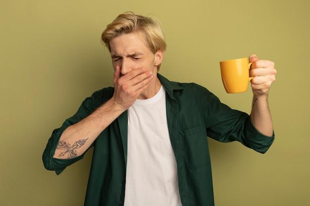 Husten junger blonder kerl, der grünes t-shirt trägt, das tasse tee und bedeckten mund mit hand hält