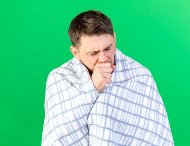 Husten junger blonder kranker slawischer mann, der in plaid eingewickelt steht, steht isoliert auf grüner wand mit kopienraum