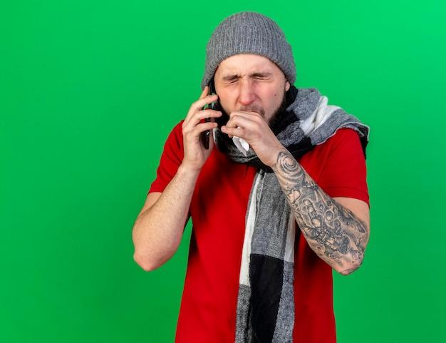 Husten junger kaukasischer kranker mann, der wintermütze und schal trägt, hält taschentuch, das am telefon spricht