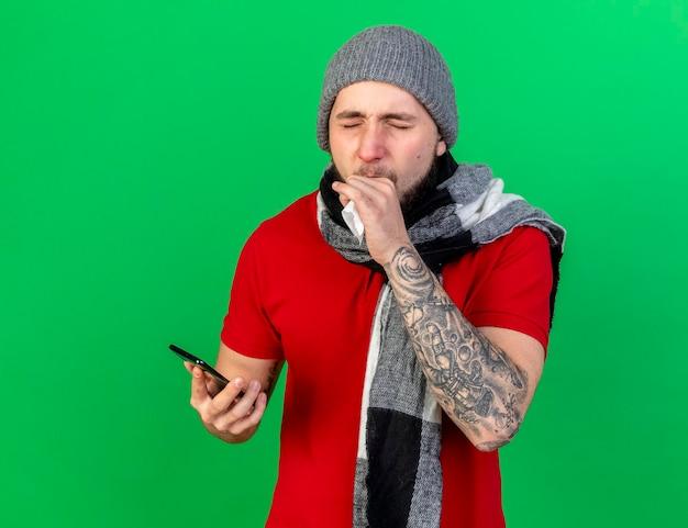 Husten junger kaukasischer kranker mann, der wintermütze und schal trägt, hält taschentuch und telefon