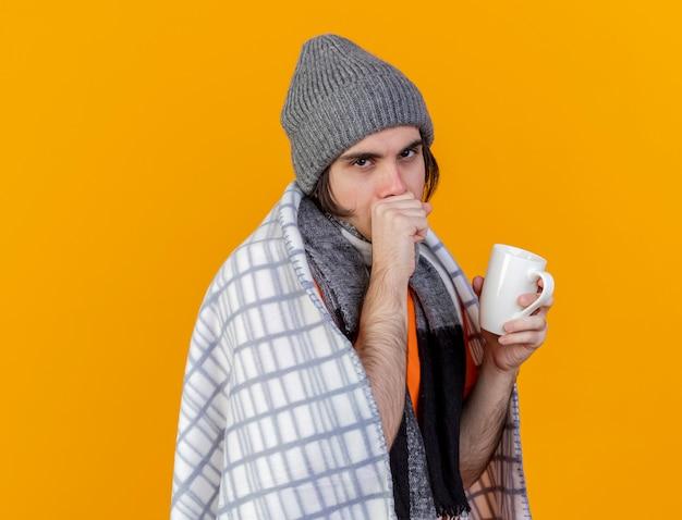 Husten junger kranker mann, der wintermütze mit schal wickelt in plaid hält tasse tee auf orange isoliert