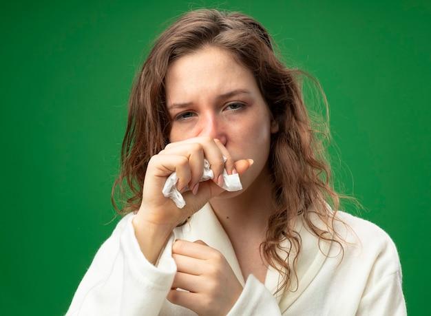Husten junges krankes mädchen, das geradeaus schaut und weißes gewand hält, das hand auf mund lokalisiert auf grün hält