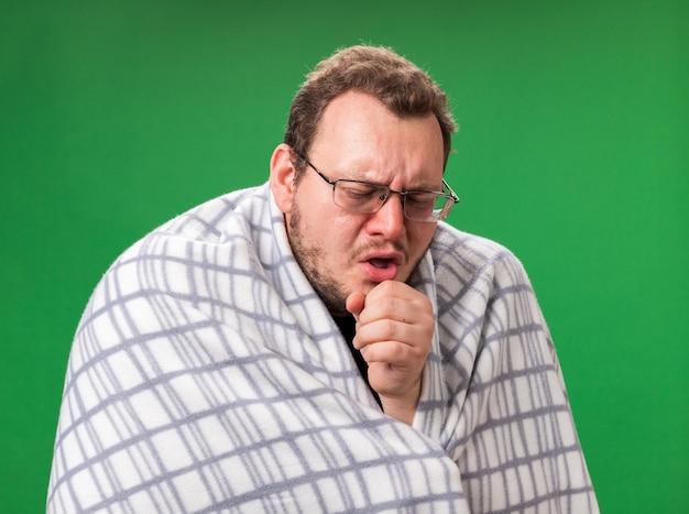 Husten mit geschlossenen augen kranker mann mittleren alters in plaid gehüllt