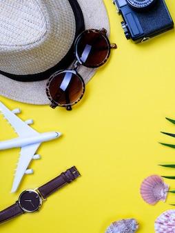 Hut, brille, muscheln und palmzweig auf einem gelben tisch