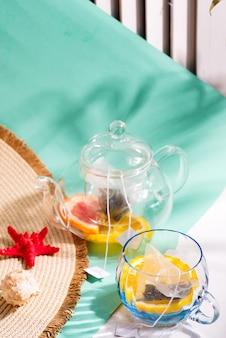 Hut mit breiter krempe und glas mit zutaten für die zubereitung von kaltem teegetränk mit frischen früchten