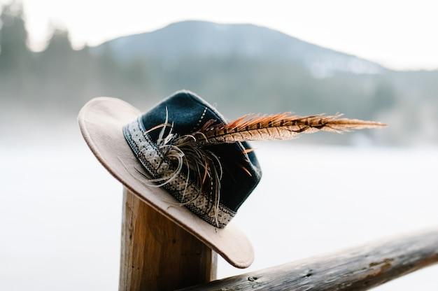 Hut mit federn handgefertigt auf einem holzzaun, eine säule im winter auf der oberfläche der berge