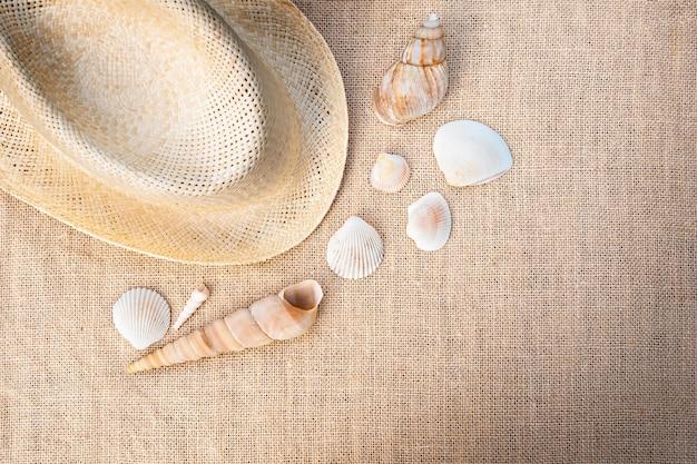 Hut mit muscheln auf dem stoff. freizeit und reisen