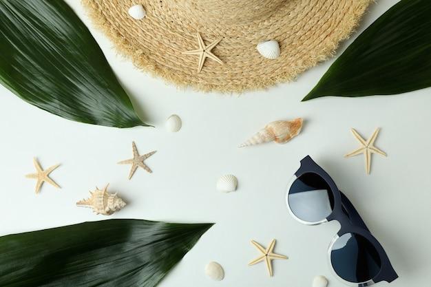 Hut, sonnenbrille, blätter, muscheln und seesterne auf weißem hintergrund