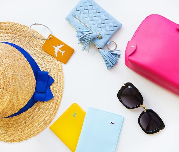 Hut, sonnenbrille, reisepass, kosmetiktasche und handtasche