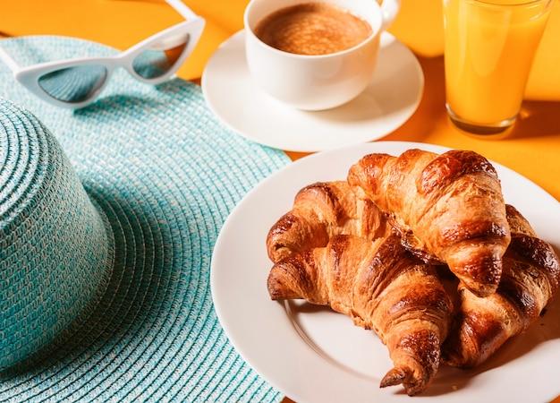 Hut, sonnenbrillehörnchen mit einem tasse kaffee und einem glas orangensaft auf einer gelben tabelle in der sonne