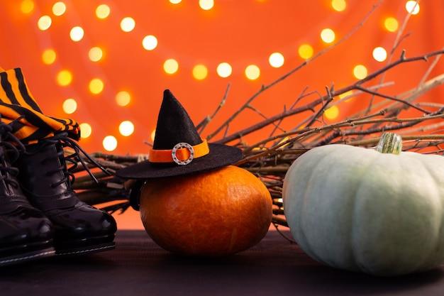 Hut, stiefel, strümpfe einer hexe mit ästen, kürbisse auf orangefarbenem hintergrund mit bokeh. halloween. platz kopieren.