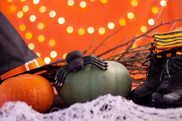 Hut, stiefel, strümpfe einer hexe mit ästen, kürbissen und einer spinne auf orangefarbenem hintergrund mit bokeh. Premium Fotos