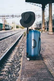 Hut thront auf einem koffer an einem bahnhof.