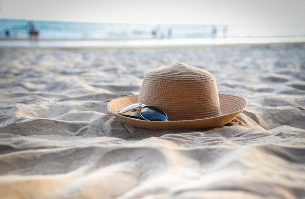 Hutsommer - strohhut fasion und sonnenbrillezubehör auf hintergrund des sandigen strandsees