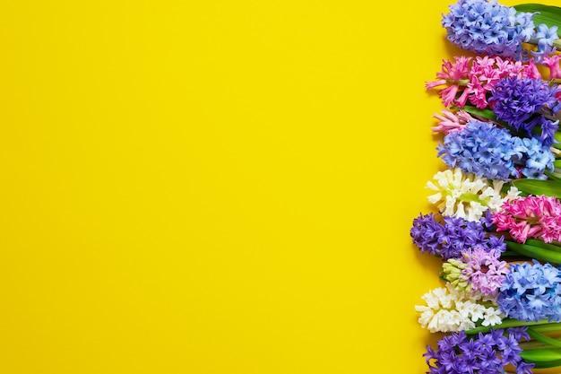 Hyazinthenblumenstrauß auf gelbem tisch. draufsicht, kopierraum.