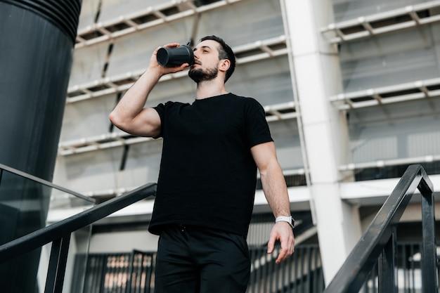 Hydratation zeit! mann trinkt wasser aus der sportflasche nach dem joggen. hartes training. achten sie auf sich selbst konzept. trinke mehr wasser. vergiss nicht, während des trainings zu trinken.
