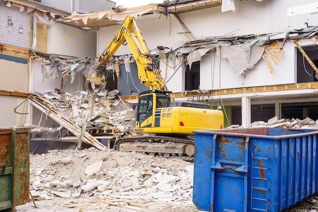 Hydraulischer bagger, der am abbruch eines alten industriegebäudes arbeitet