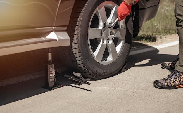 Hydraulischer wagenheber wird mit den händen in handschuhen unter das auto gestellt