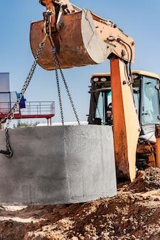 Hydraulisches kolbensystem des baggers mit einer schaufel, das an stahlseilen betonkanalring in die grube absenkt. bau oder reparatur eines kanalhauses.