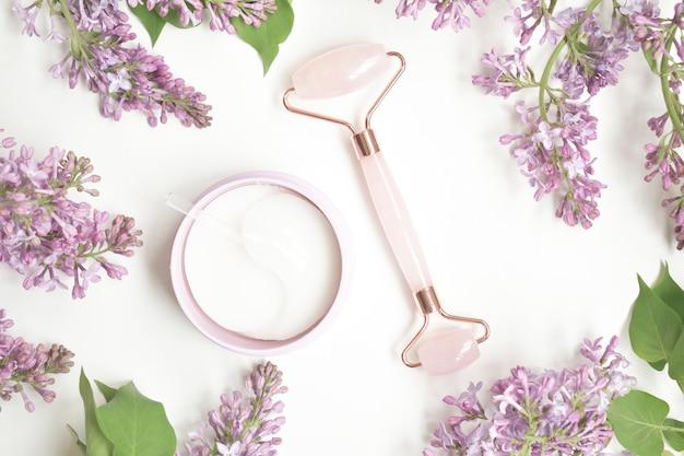 Hydrogel augenklappe mit sheabutter, um die haut um die augen zu pflegen und zu erweichen. rosa guasha massagewerkzeug auf weißer oberfläche. rosenquarz-jadewalze.