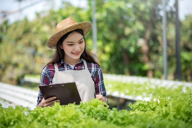 Hydroponics gemüsefarm. schöner asiatischer bauer, der hydroponischen gemüseanbau und -analyse studiert. konzept des anbaus von bio-gemüse und naturkost.