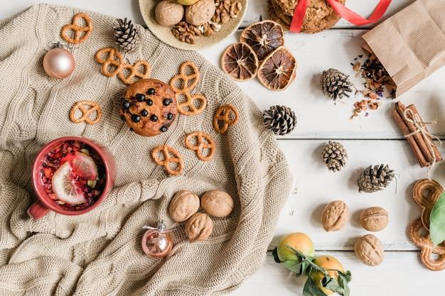 Hygge hintergrund mit gestricktem pullover, hausgemachten keksen und heißem kräutergetränk, walnüssen, tannenzapfen und gewürzen auf dem tisch