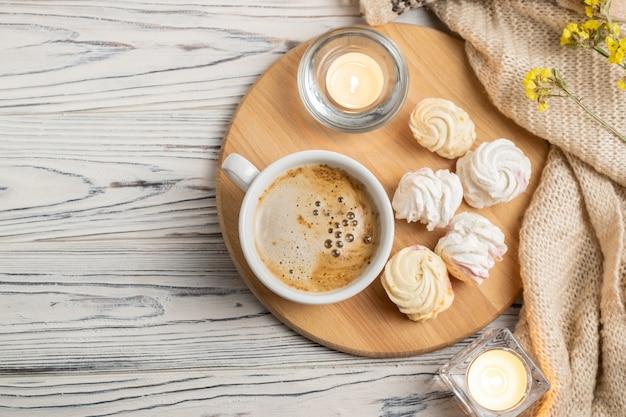 Hygge-komposition mit kaffee, kerzen, marshmallows und gestricktem plaid