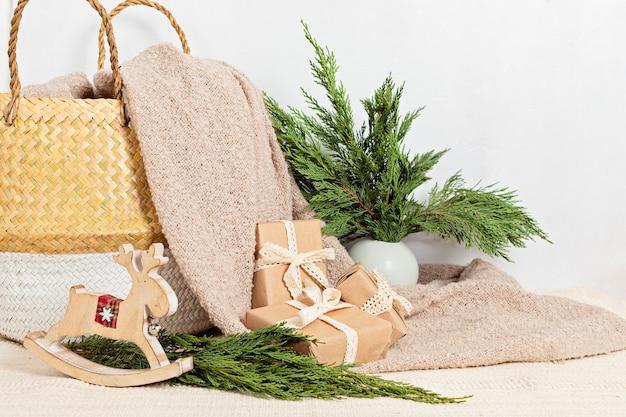 Hygge umweltfreundliche geschenke in papierverpackung mit korb und warmer, weicher decke. skandinavische weihnachten null abfall dekorationen und geschenke