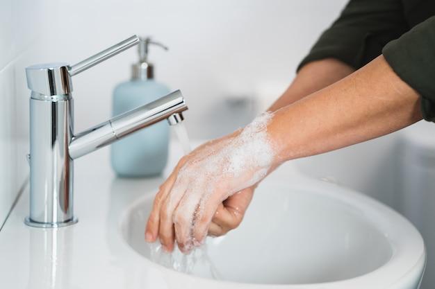 Hygiene. hände reinigen. hände waschen mit seife. junge frau, die hände mit seife über waschbecken im badezimmer, nahaufnahme wäscht. covid 19. coronavirus.