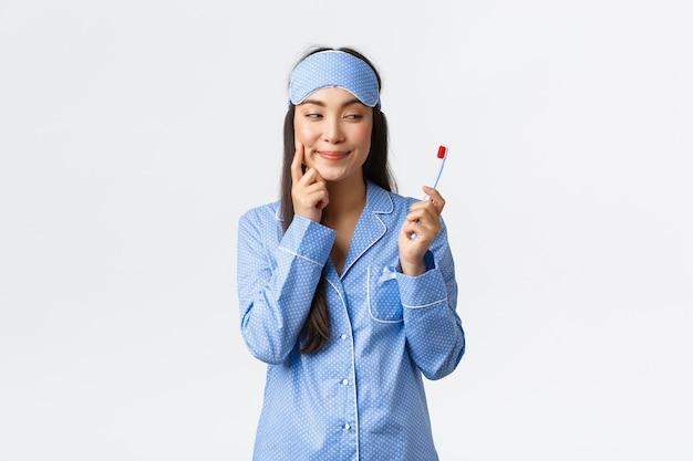 Hygiene, lebensstil und menschen zu hause konzept. schlaue und nachdenkliche hübsche asiatische mädchen in schlafmaske und schlafanzug betrachten zahnbürste und denken, haben idee, weiße wand.