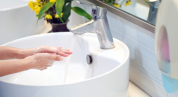 Hygienekonzept hände mit seife im waschbecken waschenabdeckung zum virenschutz