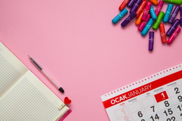 Hygienische bunte tampons auf dem rosa tischperioden- und menstruationskonzept.