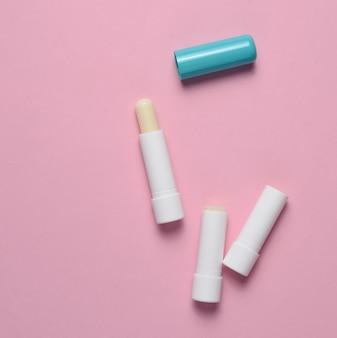 Hygienischer lippenstift auf einem rosa pastellhintergrund, draufsicht, minimalismus