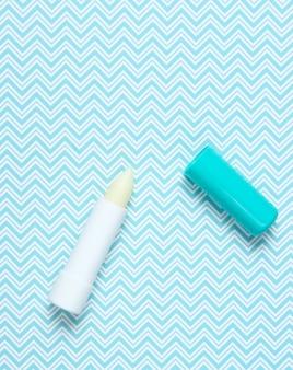 Hygienischer lippenstift auf kreativem blau, draufsicht