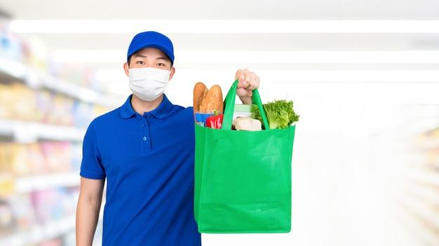 Hygienischer mann, der medizinische maske trägt, die einkaufstasche des lebensmittels im supermarkt hält, der hauslieferdienst anbietet