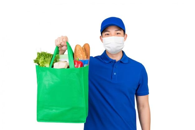 Hygienischer mann, der medizinische maske trägt, die supermarktlebensmitteleinkaufstasche hält, die hauslieferdienst lokalisiert in weiß anbietet