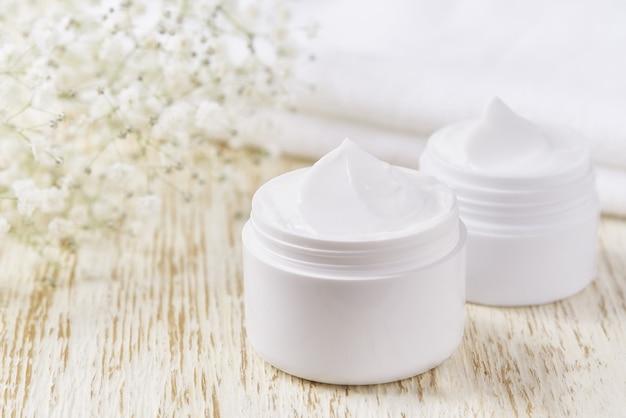Hygienisches creme-hautpflegeprodukt im plastikglas mit handtuch auf weißem tisch. hautreinigende kosmetische creme oder vitamin-spa-lotion, eine natürliche organische kräuter-anti-falten-feuchtigkeitscreme.