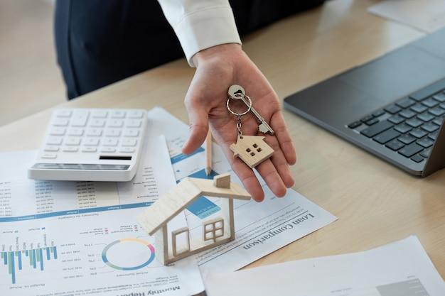 Hypothekenkonzept. frauenhand, die schlüssel mit haus geformtem schlüsselbund hält. immobilien, umzug oder miete.