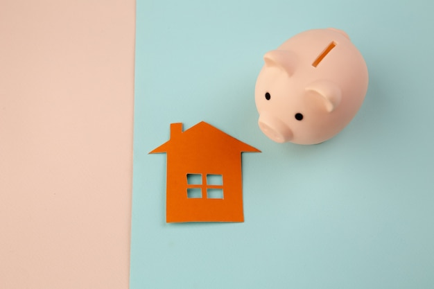 Hypothekenkonzept. kleines papierhaus neben einem rosa sparschwein auf buntem hintergrund.