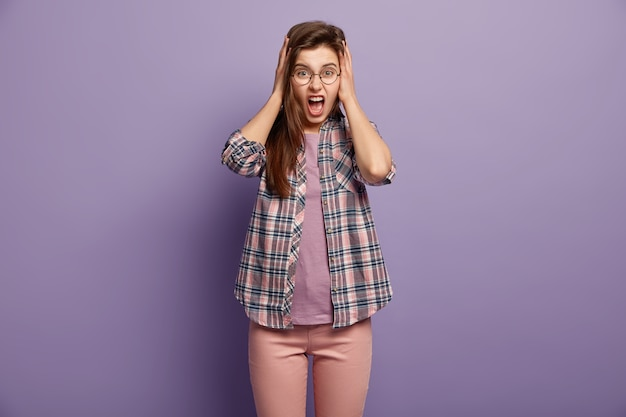 Hysterisch genervte junge frau bedeckt ohren mit hanfds, will sich nicht beschweren hören, schreit wütend, trägt eine runde brille