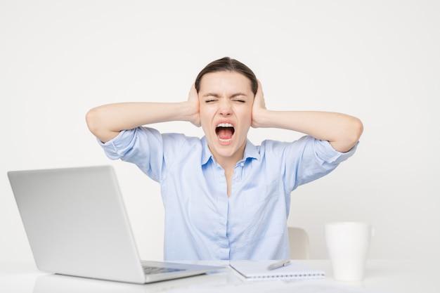 Hysterische junge geschäftsfrau, die schreit und ihre ohren mit händen bedeckt, während sie nervös ist oder sich über etwas ärgert