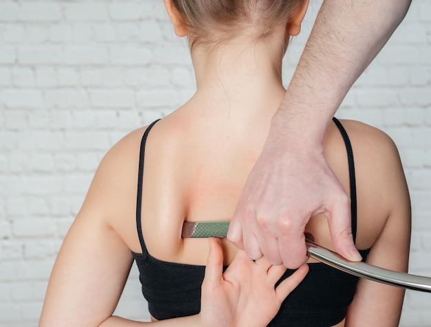 Iastm-behandlung, mädchen erhält eine weichteilbehandlung an ihrem hals mit einem edelstahlwerkzeug