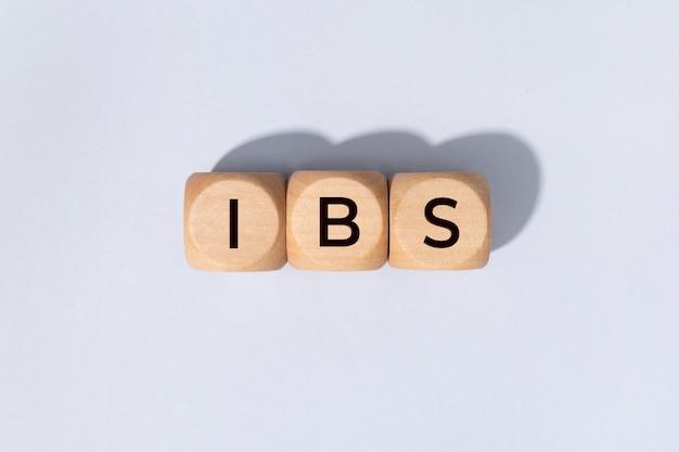 Ibs-wort auf holzblöcken auf grauem hintergrund. reizdarmsyndrom