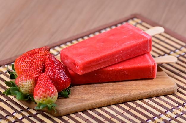 Ice pops nach mexikanischer art - strawberry paleta mexicana - eis am stiel mit erdbeeren auf einem holztisch