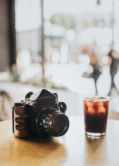 Iced americano und eine analoge 120-mm-kamera an einem café-tisch