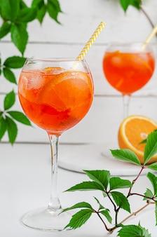 Iced aperol spritz cocktail mit orange auf weißem holzhintergrund. sommeralkoholgetränkekonzept
