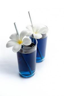Iced blaue schmetterlingserbse trinkt tropisches blumendekor. gesunde thailändische traditionelle cocktails in gläsern