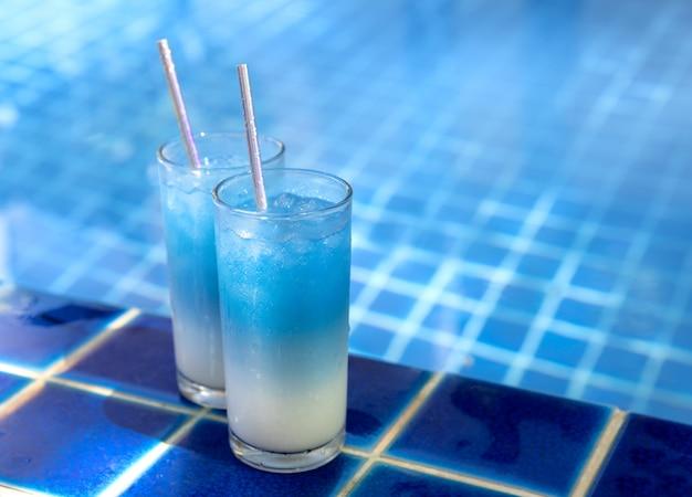 Iced blue butterfly erbse latte getränke in der nähe von schwimmbad. gesunde thailändische traditionelle cocktails in gläsern