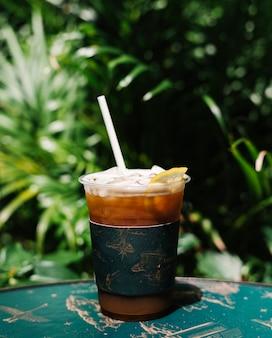 Iced cold brew-kaffee mit zitrone auf einem tisch