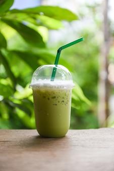 Iced drinks grüntee-smoothie - matcha-grüntee mit milch auf plastikglas